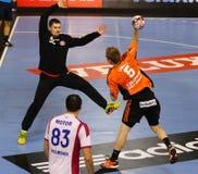 Handball game Motor Zaporozhye vs Kadetten Schaffhausen. KYIV, UKRAINE - NOVEMBER 28, 2015: Manuel Liniger of Kadetten Schaffhausen (R) attacks during VELUX EHF royalty free stock image