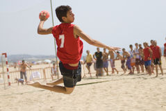Handball player jumping with the ball. Trying to score a goal on a handball beach match Royalty Free Stock Images