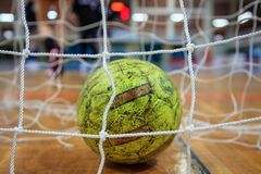 Handball ball in nets. Blurred court and athletes background. Close up view. Royalty Free Stock Photography