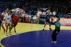 Handballspieler, der mit der Kugel springt Stockbild