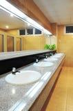 Handbasin and mirror in toilet Stock Photos