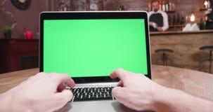 Handbediend die POV van mannelijke handen wordt geschoten die op laptop met het groene scherm typen stock video