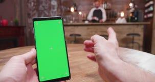 Handbediend schot van de mens die een groene het schermtelefoon in uitstekende bar met behulp van stock video