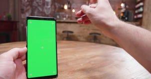 Handbediend schot van de mens met een groene het schermsmartphone in een uitstekende bar stock video