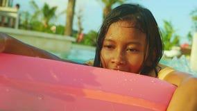 handbediend schot van jong gelukkig en leuk vrouwelijk kind die pret met opblaasbaar luchtbed in het zwembad van de vakantietoevl stock videobeelden
