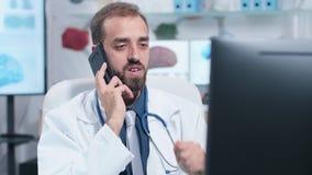 Handbediend schot van jonge arts die een gesprek op de telefoon hebben stock video
