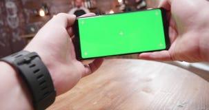 Handbediend schot van kerel die een groene het schermtelefoon houdt en sommige videospelletjes op het speelt stock footage