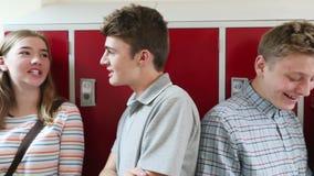 Handbediend Schot van Middelbare schoolstudenten die met Vrienden in Gang spreken stock video