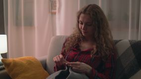 Handbediend schot van vrouwenzitting op bank en het breien in comfortabel huis stock video