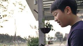 Handbediend van Aziatische jongen op een zonnige hete dag, speelt een jongen met water en geniet van het die zeer met water baden stock footage