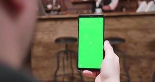 Handbediend van het houden van een telefoon met het groene scherm stock video