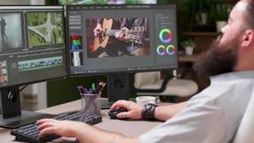 Handbediende lengte van professionele colorist die aan dubbele het schermopstelling werken stock footage