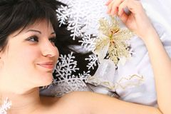 Handbell. Christmas girl Lays on white snowflakes fall on a head smile Royalty Free Stock Image