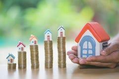 Handbescherming, huismodel bovenop stapel van geld als groei van hypothecair krediet, Concept bezitsbeheer  royalty-vrije stock afbeeldingen