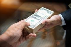 Handbojor är på de bärbar datortangentbordet och pengarna för korruption arkivfoto