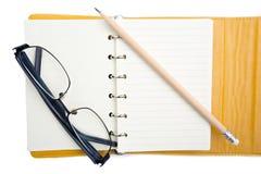 Handbok och blyertspenna för att äldre person ska skriva anmärkningen på vit backgound Arkivfoto