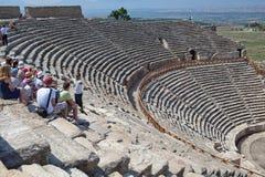 Handbok och turister i forntida amfiteater Royaltyfria Bilder