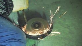 Handbok som vässar och klipper av metall vid den malande maskinen gem Vässa metall på en malande diskett arkivfilmer