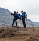 Handboken instruerar fotvandra turister på berg (2) Arkivfoton