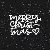 Handbokstäver för glad jul på svart bakgrund Arkivfoto