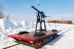 Handcar auf einer schmalen Bahn im Schnee und im blauen Himmel Stockbild