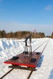 Handcar en una pista estrecha en nieve y cielo azul Fotos de archivo