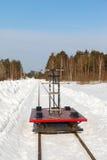 Handcar en una pista estrecha en nieve y cielo azul Foto de archivo libre de regalías
