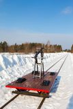 Handcar on a narrow track in snow and blue sky Stock Photos