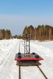 Handcar on a narrow track in snow and blue sky Royalty Free Stock Photo