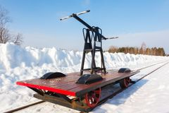 Handcar su una pista stretta in neve e cielo blu Immagine Stock