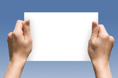 Handcard. One white card in hands on blue gradient Stock Photography