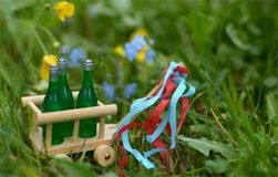 A handcart with three bottles of beer or wine for fathers day. A little handcart with three bottles of beer or wine and colorful ribbons on a wonderful spring Royalty Free Stock Images