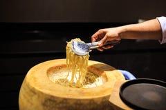 Handchef-kok het koken met kaas en spaghetti Een spaghetti van het chef-kokgebruik tong royalty-vrije stock afbeeldingen