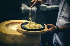 Handchef-kok het koken met kaas en spaghetti Een spaghetti van het chef-kokgebruik tong stock foto