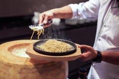 Handchef-kok het koken met kaas en spaghetti Een spaghetti van het chef-kokgebruik tong stock afbeeldingen