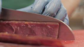 Handchefkoch, der Messer für den Schnitt des Fleisches beim oben kochen im Küchenabschluß verwendet stock footage