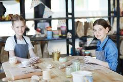 Handcraft girls. Two youthful schoolgirls looking at you while siting by table and kneading clay to make handcraft stock image