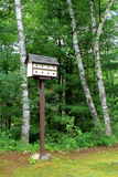 Handcrafted birdhouse on corner of woodsy lawn. Tall wood pole with handcrafted birdhouse, standing on corner of woodsy lawn, surrounded by birch trees Stock Photos