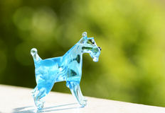 Handcrafted blown glass Miniature Schnauzer puppy dog. A gorgeous handcrafted, Russian hand blown blue glass figurine of a Miniature Schnauzer puppy dog sitting Royalty Free Stock Images