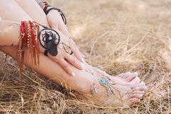 Handcrafted bracelets on a woman legs and hands, dreamcatcher jewelry. Close up, white pedicure and manicure, boho chic style, sunny outdoor photo on a straw Royalty Free Stock Photography