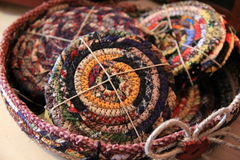 Handcrafted coasters in woven basket Stock Images