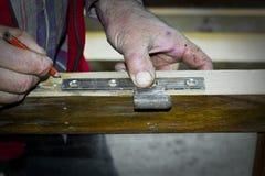 Handcrafted drewniany drzwi w ciesielce Mężczyzna instaluje zawias ręcznie Obrazy Stock