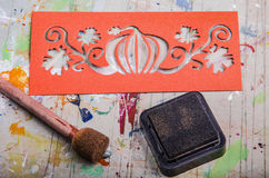Handcrafted Halloween. Orange paper-cut and ink pad lying on the artist's table ready for Halloween handcraft Royalty Free Stock Photos