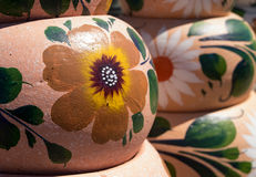 Handcrafted Mexican pottery. Stacked pottery with hand painted floral designs in open air market Stock Photography