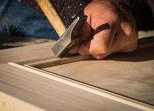 Man hammering nail into wood with sunlight. Stock Photo