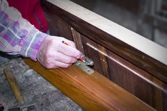 Handcrafted wooden door in carpentry. Man installing hinge manually. Stock Images