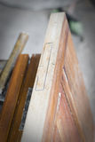 Handcrafted wooden door in carpentry. Man installing hinge manually. Stock Photos