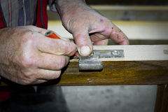 Handcrafted wooden door in carpentry. Man installing hinge manually. Stock Photography