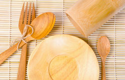 Handcrafted wooden kitchen utensils on bamboo weave Royalty Free Stock Images