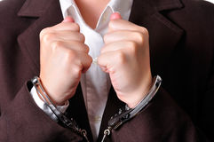 Handcuffed. Closeup of an handcuffed businessperson in a brown suit Royalty Free Stock Photo